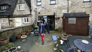 People walking out of their home into a flooded garden