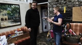 Prime Minister David Cameron meets a flood victim in Buckfastleigh, Devon
