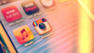 A mobile phone showing the Instagram icon