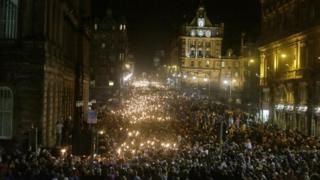 People take part in a torchlight procession through Edinburgh as part of the pre Hogmanay celebrations.