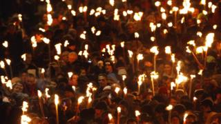 People walk down North Bridge carrying lit torches during the annual torchlight procession to mark the start of Hogmanay