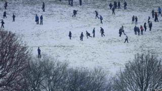 School children play in a snow covered field near Halifax