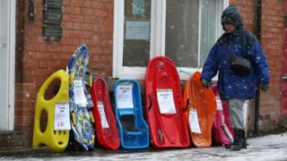 A woman walks past a selection of sledges in Nottinghamshire