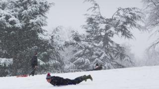 A man sledging in the snow in Wollaton Park, Nottingham