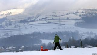 A man pulls a young girl on a sledge through a snow covered field near Halifax
