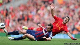 Dean Whitehead of Stoke City tackles Luis Suarez of Liverpool