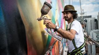 An artist close to the side of the building sprays the wall with an airbrush.