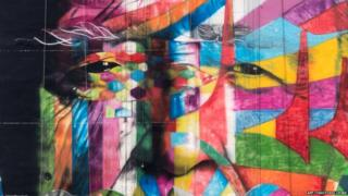 A close up of the mural shows a man's face merged with abstract shapes and bright colours.