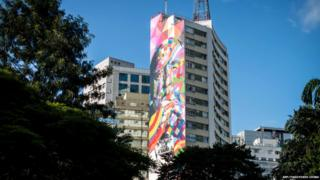 An ordinary concrete tower block in Sao Paulo with one side brightly painted.