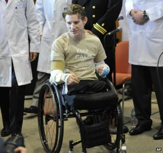 Brendan Marrocco wheels himself into a news conference followed by surgeons