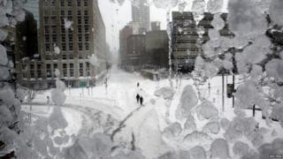People walk down snow covered streets in Boston.