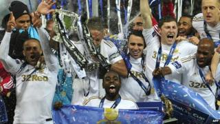 Swansea City players celebrate with Capital One Cup final trophy.