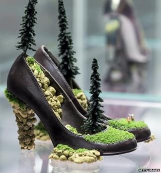 High heels with rocks and miniature trees growing out of them.