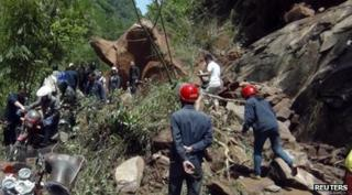 Rescuers try to remove rocks blocking a road