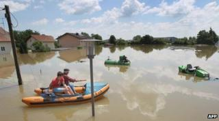A man and a boy in a rubber boat make their way through the flooded village of Deggendorf, southern Germany