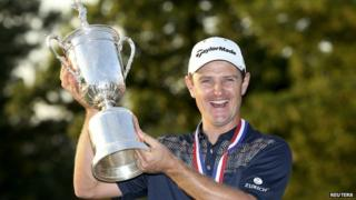 Golfer Justin Rose lifts the trophy after winning the US Open golf championship.