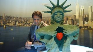 Artist Nathan Sawaya poses with one of his many Lego creations. This one is based on the Statue of Liberty.