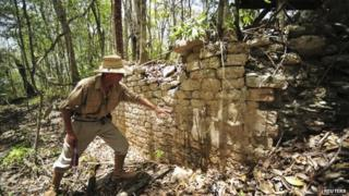 An archaeologist inspects a wall at a site where they have found an ancient Maya city
