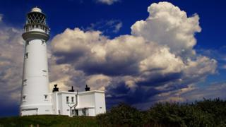 A white lighthouse and large white clouds in a blue sky above.