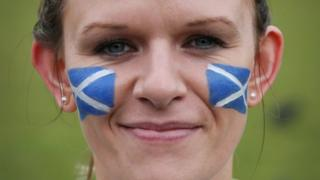 Woman with Scottish flag face paint.