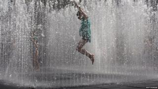 Children jump in the fountain on the southbank of the River Thames in London.