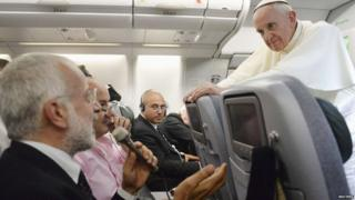Pope Francis answers journalists' questions during a flight.