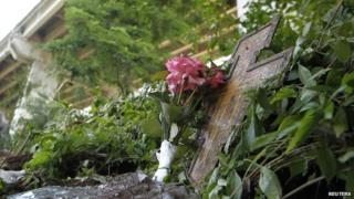 Flowers and crucifix placed near crash site