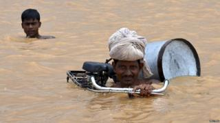 A flood-affected man with his bicycle moves to a safer place. He is submerged to his shoulders in water.