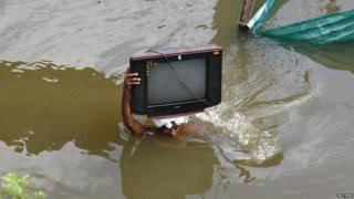 A man carrying his television through water.