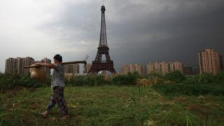 A farmer walks past a replica of the Eiffel Tower in Zhejiang Province, China.