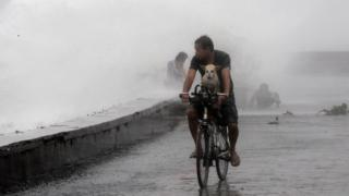 man with dog cycling past waves