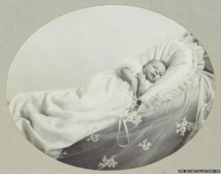 Previously unpublished family photograph issued by the Royal Collection of Queen Elizabeth II in her cot aged five weeks in 1926.