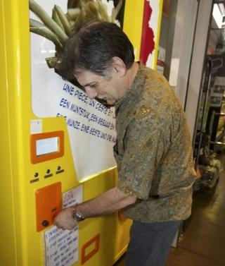 A man puts a coin in a large yellow vending machine.
