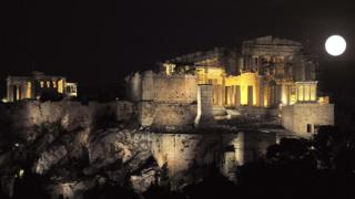 Full moon rises next to the ancient Acropolis in Athens