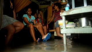 A family sit inside their flooded house, south of Manila in the Philippines