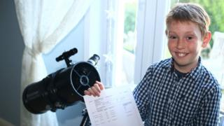 Monty poses with a telescope and his GCSE results