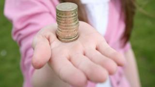 Girl holding a stack of pound coins