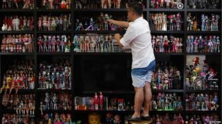 Man places a doll with his collection of thousands on a shelf.