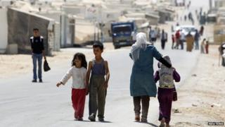 Child refugees walking near to a camp