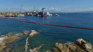 From a distance, the Costa Concordia surrounded by cranes, all floating on the calm waters.