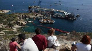 A group of onlookers sit on nearby land and watch the salvage attempt of the Costa Concordia.