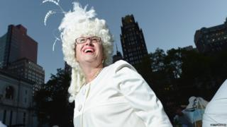 A woman in a big white wig.