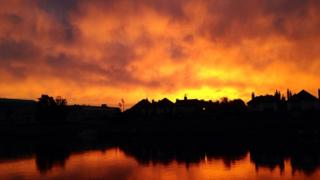 A flaming yellow and orange cloudy sky above a silhouetted skyline of roofs and chimneys.