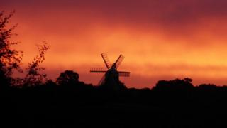 A windmill against a pink and orange cloudy sky.