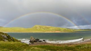 A rainbow stretches across water to green, hilly land. Grey sky above, and a faint second rainbow.