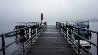 A pier with a life ring and a boat next to it. Fog over water behind.