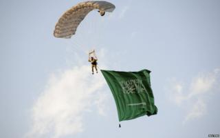 A parachutist descends from the sky carrying the national flag of Saudi Arabia