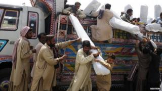 Pakistani earthquake survivors receive tents at a distribution point in the devastated district of Awaran