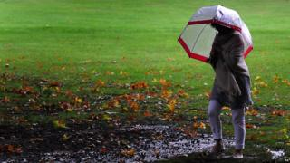 A woman braves the rain at Rufford Abbey, Ollerton, Nottinghamshire.