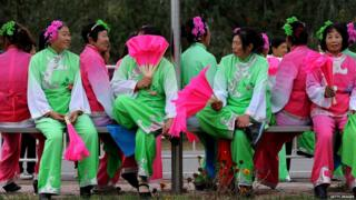 A group of Chinese women dressed in traditional costumes rest on a bench as they wait to perform for the cyclists during the third stage of the 2013 Tour of Beijing